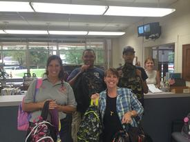 Beltsville VFD members Margie Dickey, Al Diagne and Daniel Tyler presenting backpacks to St. Joseph's Principal Mrs. Anne Marie Miller.